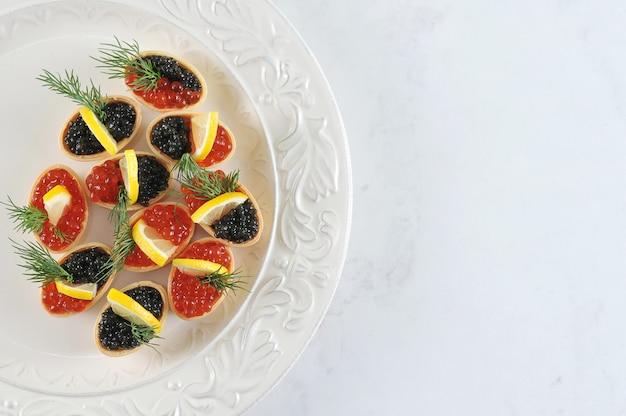Canapés com limão e caviar preto e vermelho