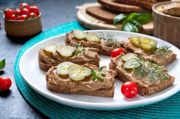 Canapés com patê de fígado de frango e pepinos em conserva no pão de centeio. aperitivo saboroso e saudável