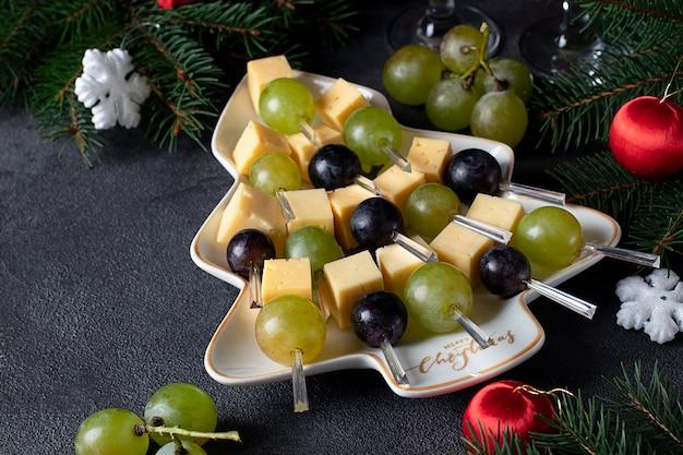 Canapés com queijo e uvas serviram no prato como árvore de natal, em fundo cinza escuro. lanche de festa de ano novo
