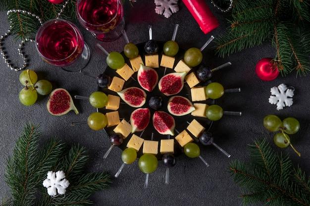 Canapés com queijo, uvas e figos. lanche de festa de natal para vinho em fundo escuro