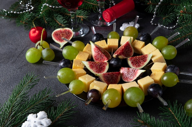 Canapés com queijo, uvas e figos. lanche de festa natalina para vinho em fundo cinza escuro