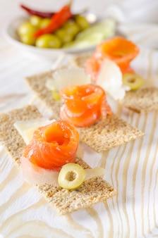 Canapés de aperitivo delicioso com salmão e queijo.