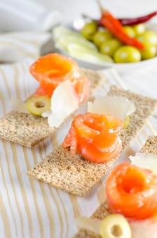 Canapés de aperitivo delicioso com salmão e queijo
