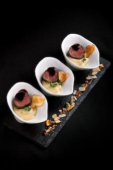 Canapés de atum com molho de vinho tinto e purê de aspargos com feijão