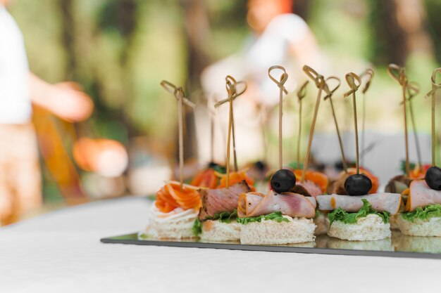 Canapés de carne na mesa branca no catering para empresas