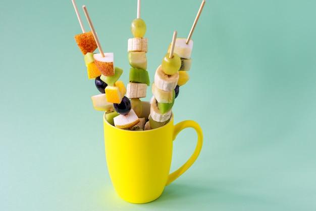 Canapés de frutas para um buffet em uma xícara. guloseimas doces para um feriado, aniversário, aniversário.
