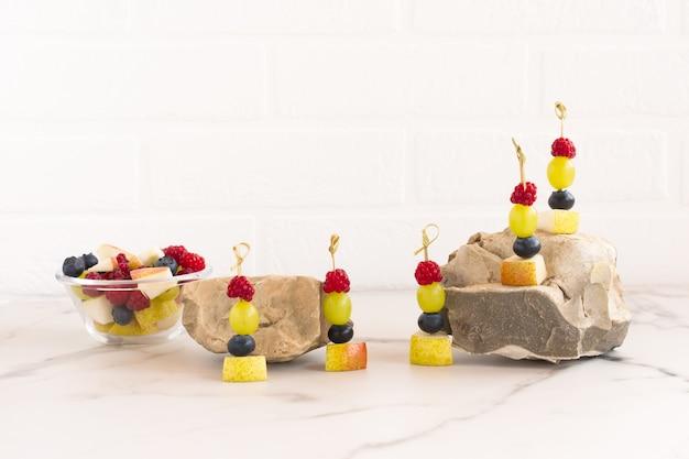 Canapés de frutas suculentas em espetos, uma mistura de frutas cortadas em uma tigela de vidro. composição em pedras e mesa de mármore. vista frontal.
