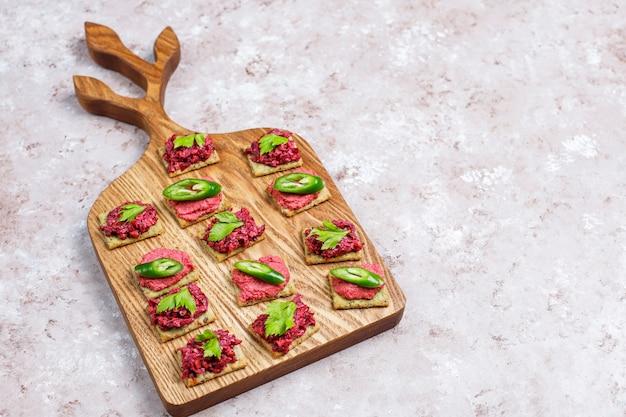 Canapés de hummus de beterraba com fatias de pimenta verde e salsa no tabuleiro na superfície de luz