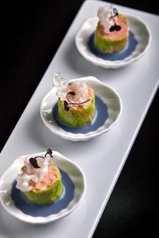 Canapés de salmão assados com molho, em pires pequenos brancos, comida de catering de conceito.