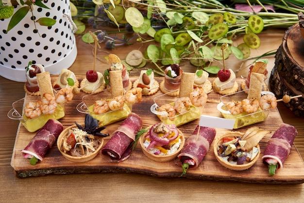 Canapés diferentes com salmão defumado, pepino, tomate, queijo, carne. mesa de buffet de café da manhã com uma variedade de lanches. buffet servido mesa com lanches, frutas, canapés, doces e aperitivos.