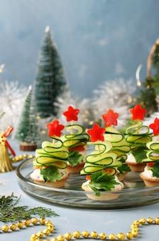 Canapés festivos em forma de árvores de natal feitas de pepinos e estrelas de pimentão em um fundo azul claro com dois copos de vinho, closeup
