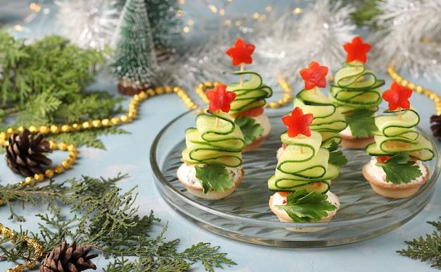 Canapés festivos em forma de árvores de natal feitos de pepinos e estrelas de pimenta vermelha