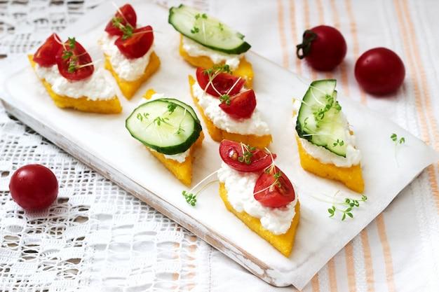 Canapés vegetarianos de polenta com queijo, legumes e agrião. estilo rústico.