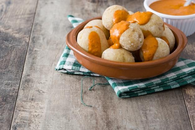 Canárias batatas com molho mojo na mesa de madeira. copie o espaço