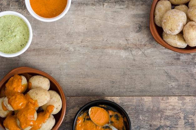 Canárias batatas com molho mojo na mesa de madeira.
