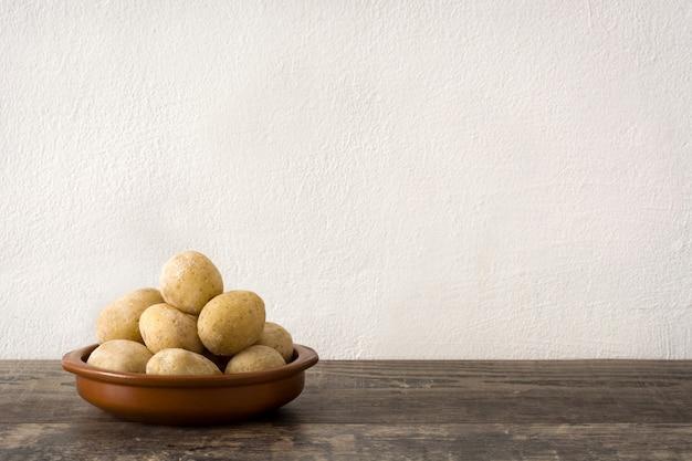 Canárias batatas na mesa de madeira.