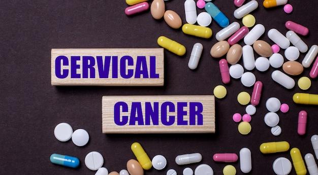 Câncer colorido é escrito em blocos de madeira perto de pílulas multicoloridas. conceito médico