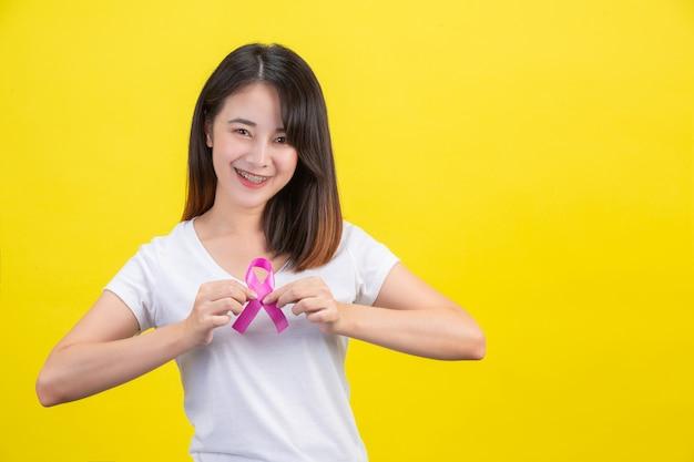 Câncer de mama, uma mulher em uma camiseta branca com uma fita de cetim rosa no peito, um símbolo para a conscientização do câncer de mama