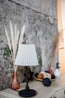 Candeeiro de mesa e vasos no canto aconchegante da mesa branca em uma casa com flores secas em um vaso