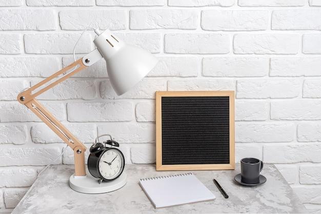 Candeeiro de mesa, quadro de carta em branco vazio, caderno e despertador em cima da mesa, no contexto de uma parede de tijolos brancos. local de trabalho, vista frontal, simulação.