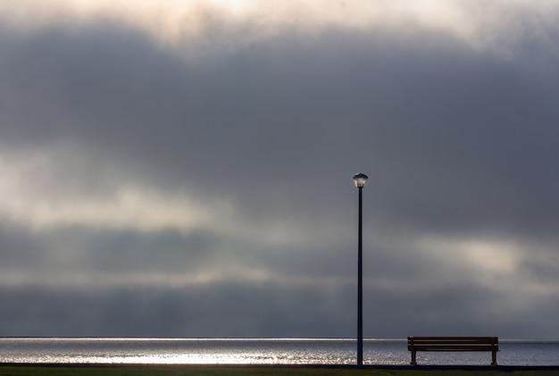Candeeiro de rua e banco em frente ao dramático fundo do céu com nuvens