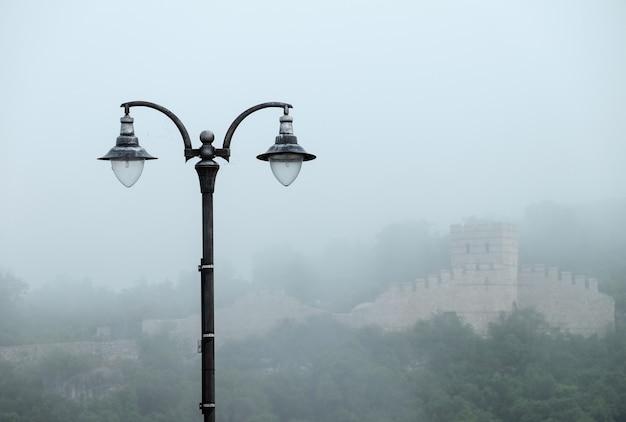 Candeeiro de rua e parede de castelo no nevoeiro na bulgária