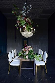 Candelabro de christal rico paira sobre a mesa de jantar com rosas vermelhas e vegetação