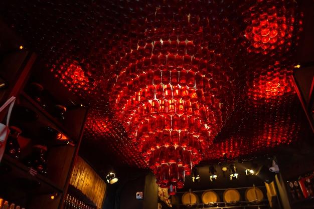 Candelabro vermelho no teto feito de garrafas de vidro. o conceito de decoração do interior de um bar