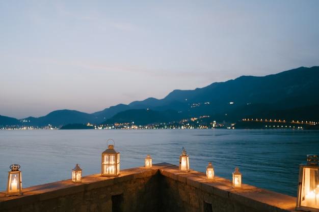 Candelabros-lanternas em uma fronteira de pedra com vista para as montanhas e a costa de montenegro, na cidade de budva.