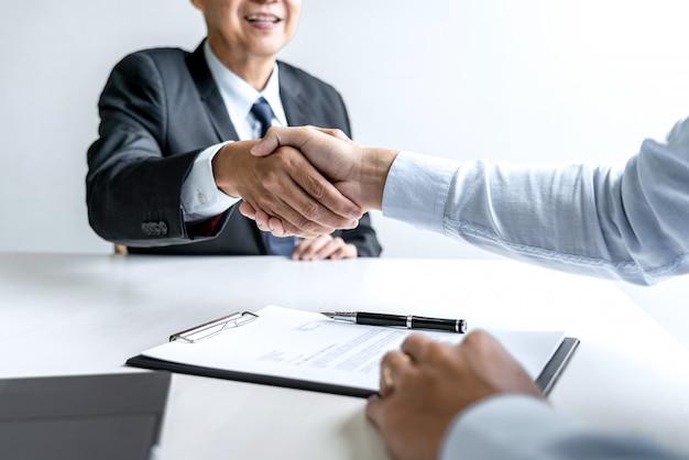 Candidato apertando a mão do empregador após entrevista de emprego