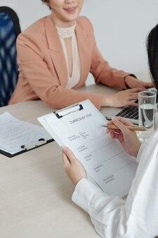 Candidato preenchendo formulário de curriculum vitae na mesa do gerente de recursos humanos que está trabalhando no laptop