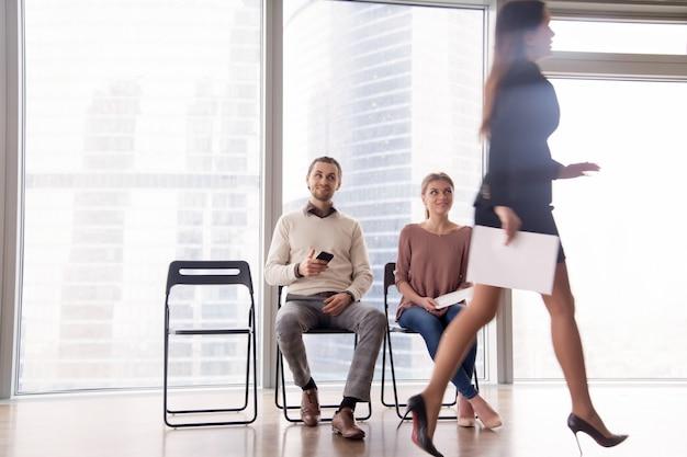Candidatos a emprego se regozijam com concorrente feminina caminhando após entrevista malsucedida