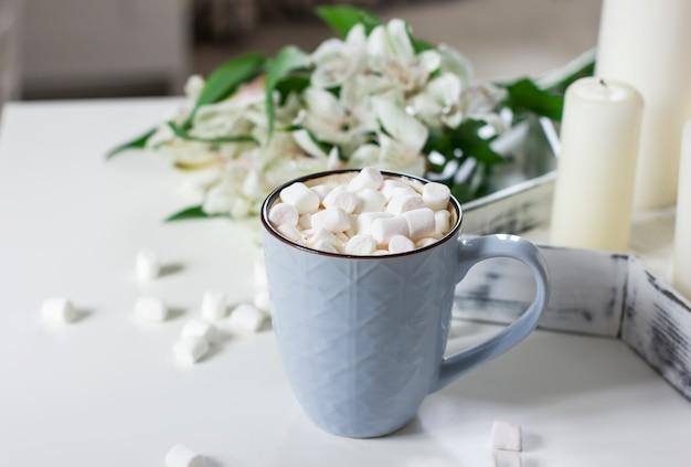 Caneca azul com cacau, café, marshmallows na mesa branca com decoração