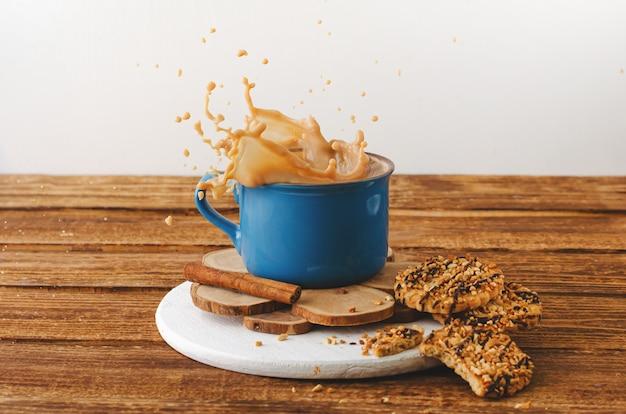 Caneca azul com salpicos de café e biscoitos no fundo de madeira.