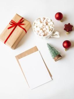 Caneca branca com bebida quente e marshmallows, cartão de papel para carta, envelope e decoração de natal