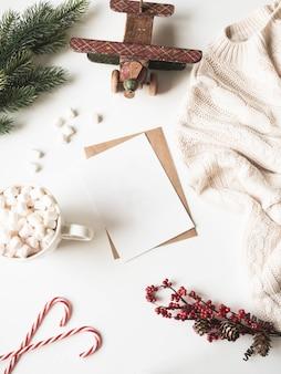 Caneca branca com bebida quente e marshmallows, cartão de papel para carta, envelope, manta de malha e decoração de natal