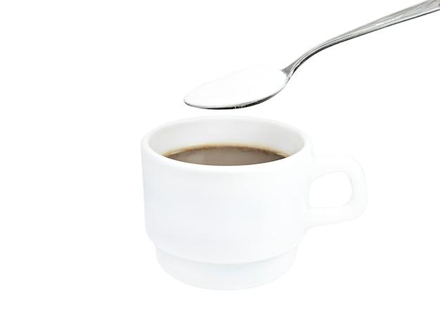 Caneca branca com café e colher com isolado de creme seco