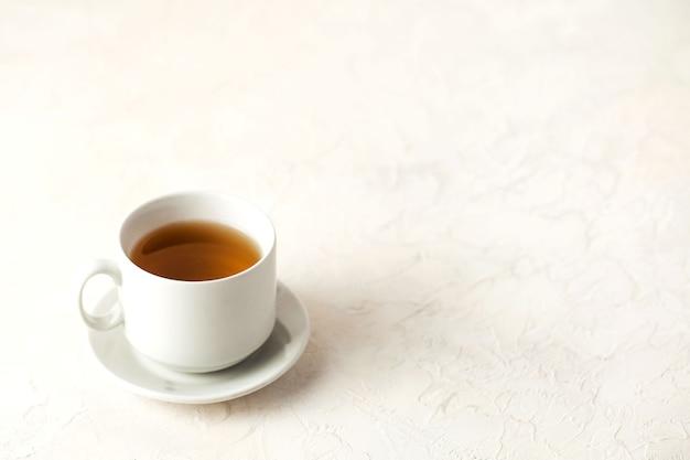 Caneca branca com chá em um fundo claro com um lugar para inserir texto