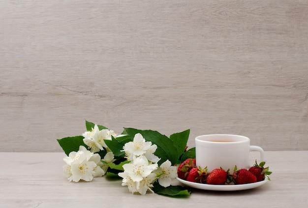 Caneca branca com chá, um ramo de jasmim e morango