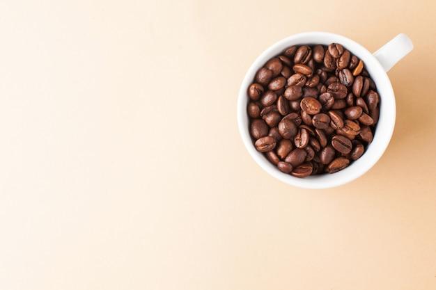 Caneca branca com grãos de café arábica no canto superior de uma foto horizontal, muito espaço para texto. café cor de fundo.