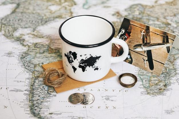 Caneca branca com um mapa do mundo no fundo do mapa-múndi.