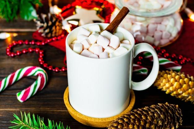 Caneca branca de cacau com marshmallows, pirulitos, cones de abeto, galho de árvore de natal, guirlanda e floco de neve na mesa de madeira