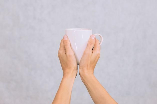 Caneca branca de café, chá nas mãos de uma menina. sobre um fundo branco.