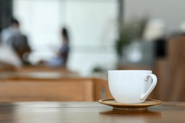Caneca branca de café no piso de madeira no café.