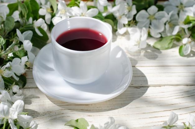 Caneca branca de chá em uma mesa de madeira, flores de maçã