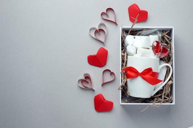 Caneca branca, doçura e decoração vermelha em caixa de presente em fundo cinza