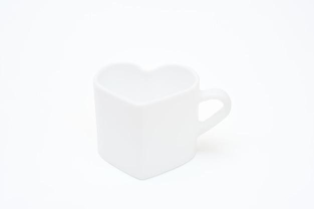 Caneca branca em forma de coração em fundo branco