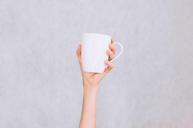 Caneca branca para café, chá na mão da menina. sobre um fundo branco.