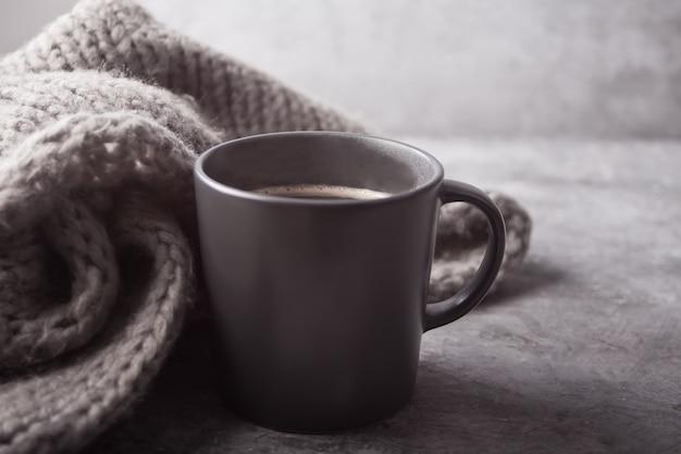 Caneca cinza de café e cachecol cinza em cima da mesa cinza