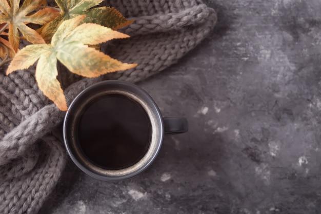 Caneca cinza de café e cachecol na mesa cinza